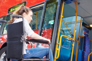 woman in wheelchair getting on a bus